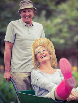 Older Angleton TX couple smiles and shows off their partial and implant supported dentures near Lake Jackson, TX.